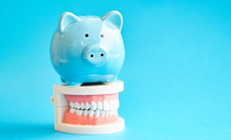 piggy bank atop model teeth for cost of dental implants in Massapequa Park