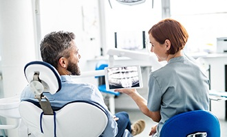 Dentist and patient discuss dental implants in Massapequa Park