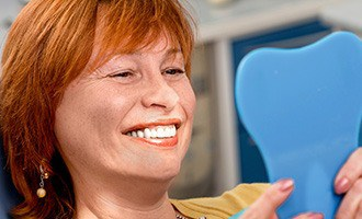 Woman admiring her new dental implants in Massapequa Park