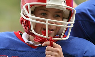 Young boy with sportsguard wearing football helmet