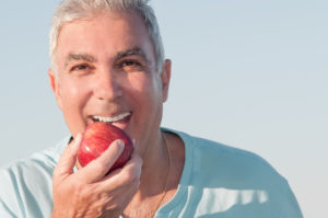 older man preparing to eat apple