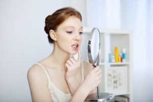 woman looking at her mouth in the mirror