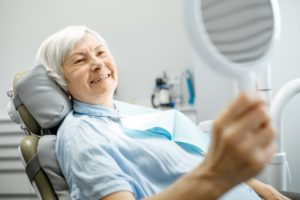 older woman admiring her smile in hand mirror